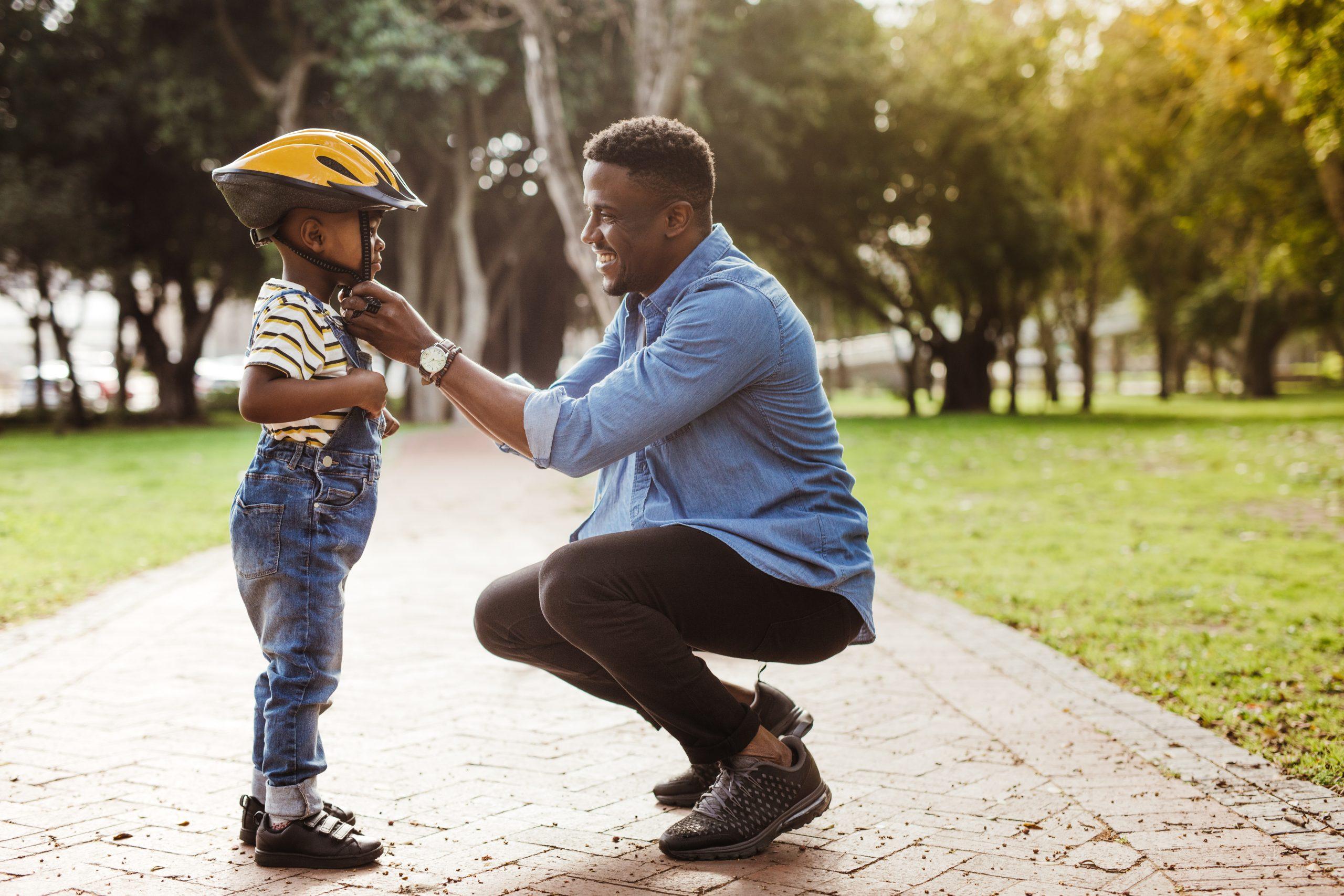 Dad Helping Little Kid with Helmet